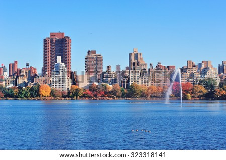 Fountain over lake in New York City Manhattan Central Park with skyscraper buildings and colorful Autumn foliage and clear blue sky. - stock photo