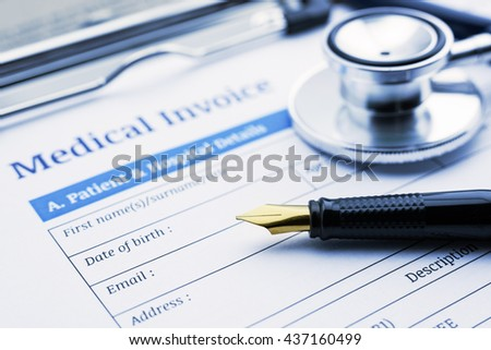 Fountain pen, a chest-piece of a stethoscope and a medical invoice on a clipboard. - stock photo