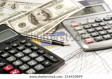 Fountain pen and calculator on the financial graph - stock photo