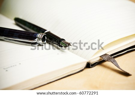 Fountain pen and calendar in composition in color - stock photo