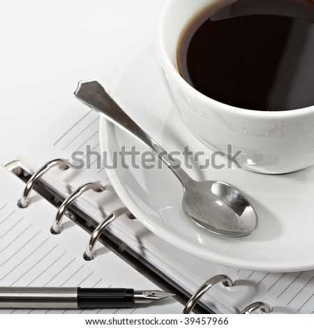 fountain pen and diary with a coffee cup