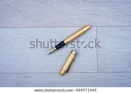 Fountain Pen and its cap on the floor. - stock photo