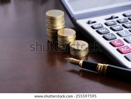 Fountain pen and Money coins stack and calculator for finance concept - stock photo