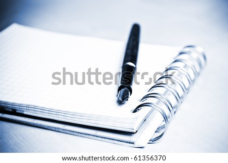 Fountain pen and notebook in composition in blue tone - stock photo