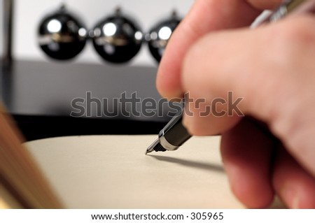 Fountain Pen and Pad With Newtons Balls in The Background. - stock photo