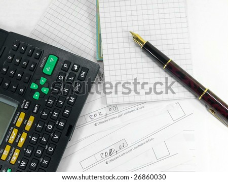 Fountain pen calculator notepad and bills over white - stock photo