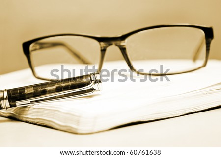 Fountain pen calendar and glasses in composition in sepia tone