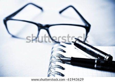 Fountain pen glasses and notebook in composition in blue tone - stock photo
