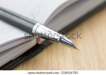 Fountain pen in a notebook - stock photo