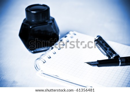 Fountain pen ink bottle and notebook in composition blue toned