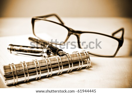Fountain pen notebook and glasses in composition i sepia tone