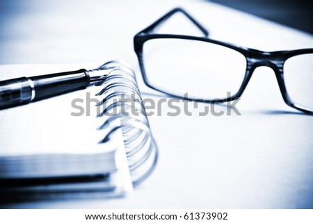 Fountain pen notebook and glasses in composition in blue tone