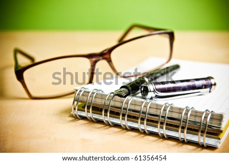 Fountain pen notebook and glasses in composition in color - stock photo