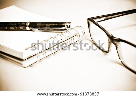 Fountain pen notebook and glasses in composition in sepia
