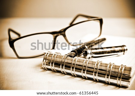 Fountain pen notebook and glasses in composition in sepia tone