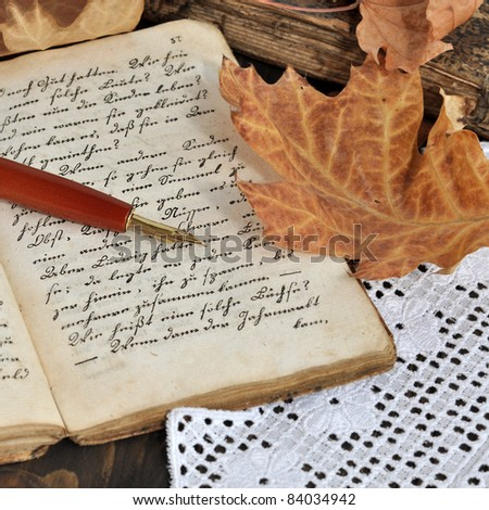 Fountain pen on old handwritten book with autumn leaves on a lacy tablecloth - stock photo