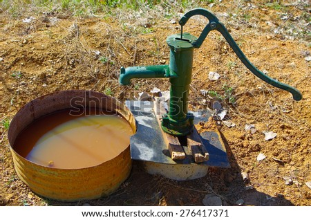 Fountain water with a hand pump - stock photo