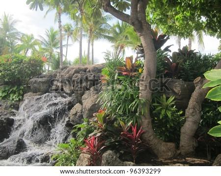 fountain with trees at waikiki beach walkway - stock photo