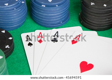 Four aces and poker stacked chips of many colors
