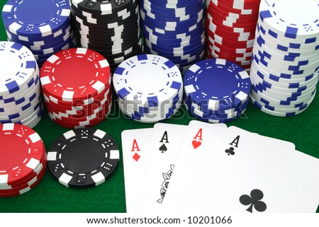 four aces besides several piles of gambling chips