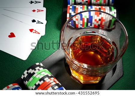 Four aces, glass of whiskey and chips on a poker table - stock photo