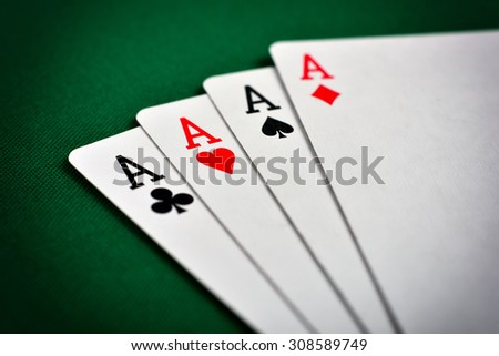 Four aces, including spades, hearts, clubs and diamonds - stock photo