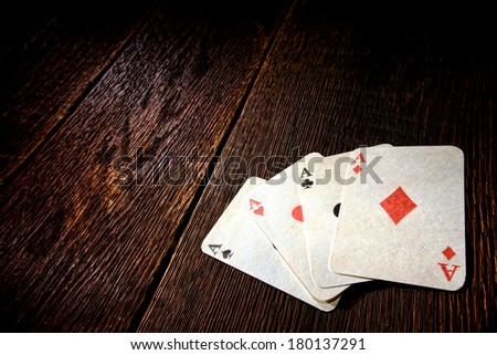 Four aces vintage poker game playing cards on a weathered wood table in an old western frontier gambling establishment saloon - stock photo
