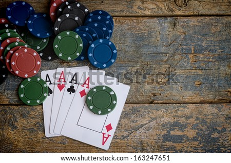 four aces with casino chips on wooden table - stock photo