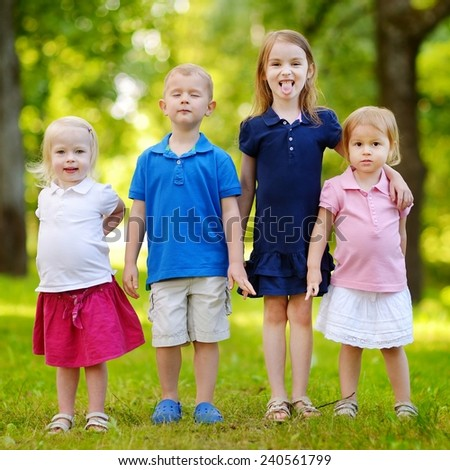 Four adorable little kids outdoors at summer day - stock photo