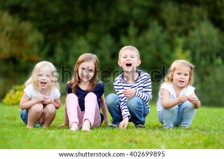 Four adorable little kids outdoors at warm summer day - stock photo