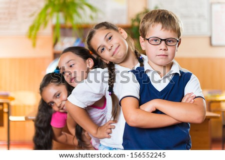 Four adorable schoolchildren standing in classroom at school - stock photo