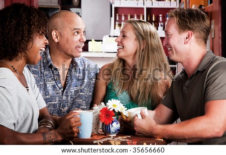 Four adult friends meeting in a coffee house - stock photo