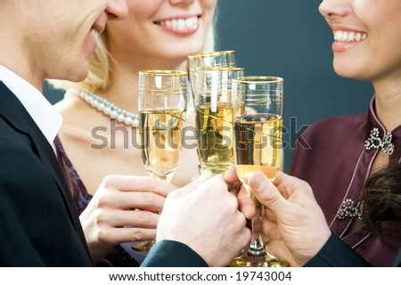 Four adults clink glasses with champagne - stock photo