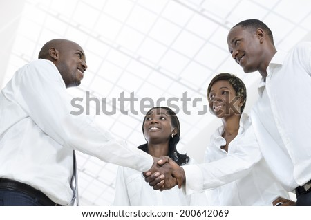 Four african business partners shake hands, Studio Shot