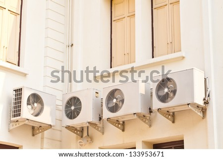 Four air condition box on side of building - stock photo