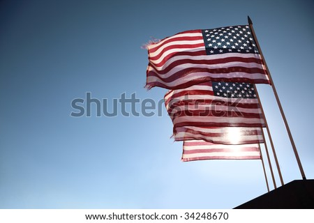 Four American flags waving over blue sky - stock photo