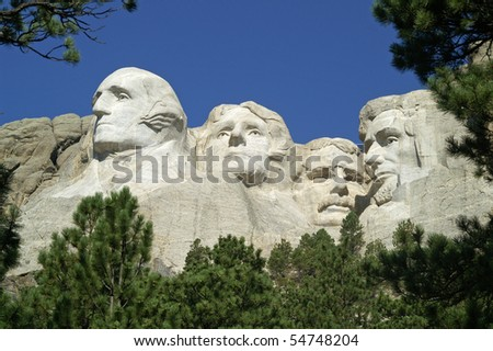 Four American Presidents framed by bushes and ponderosa pine trees at Mount Rushmore National Memorial, South Dakota - stock photo