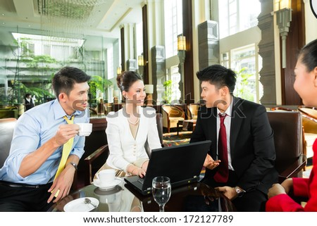 Four Asian Chinese office people or businessmen and businesswomen having a business meeting in a hotel lobby discussing documents on a tablet computer while drinking coffee  - stock photo