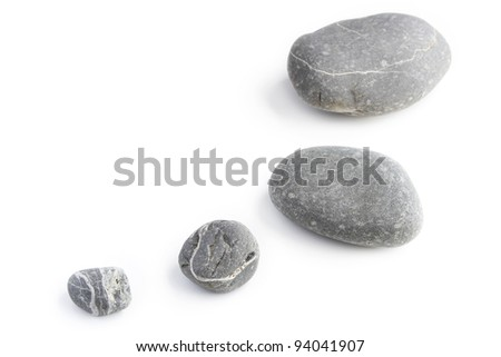 Four assorted size rocks on plain background - stock photo