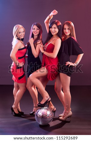 Four attractive females with disco ball at the club - stock photo