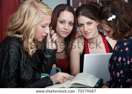 Four attractive girls busy with a school project