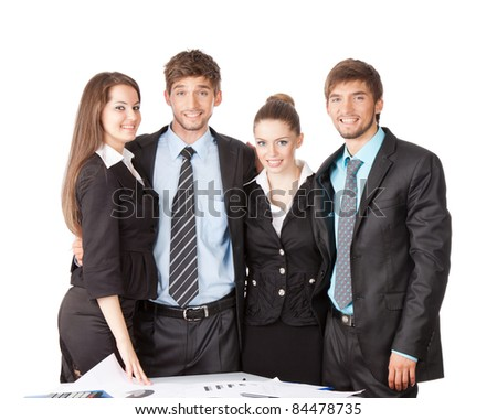 four attractive positive smile young business people in elegant suits standing at the desk with papers, Isolated over white background - stock photo