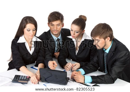 four attractive positive young business people in elegant suits sitting at desk in front of a laptop computer with papers, document point finger working in team together Isolated over white background - stock photo