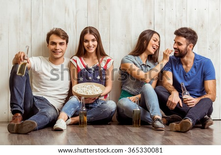 Four attractive young friends sitting on the floor, keeping beer and popcorn, smiling - stock photo