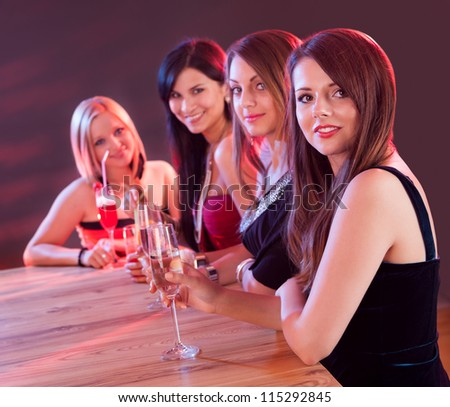 Four attractive young lounge ladies seated at a bar counter in a nightclub enjoying cocktails together - stock photo