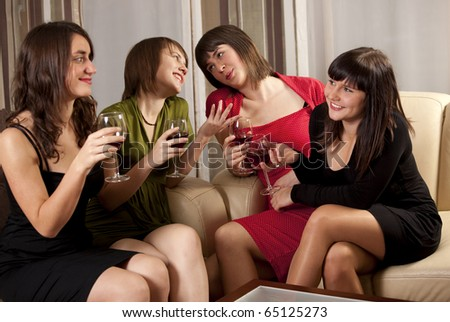 Four attractive young women in evening wear with wine - stock photo