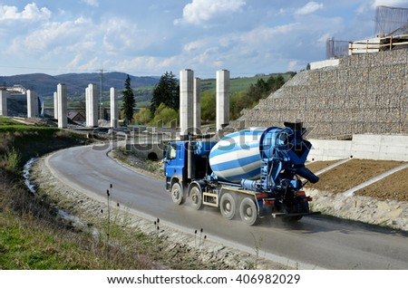Four axles truck mixer on the road near by highway under construction - stock photo