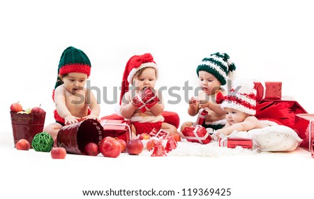 Four babies in xmas costumes playing among gifts - stock photo