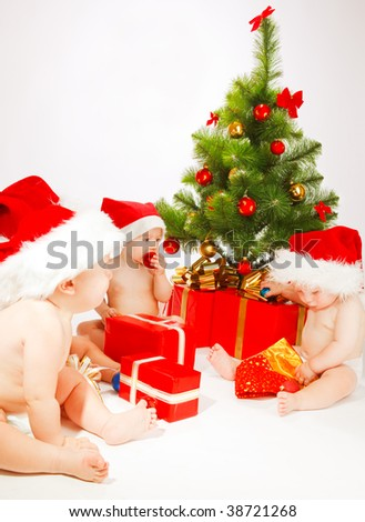 Four baby friends  sitting beside Christmas tree - stock photo