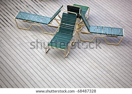 four back to back lounge chairs on a deck - stock photo